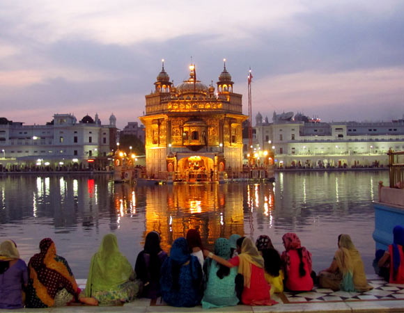 Indian women sat by a lake overlooking a temple in Amritsar_2