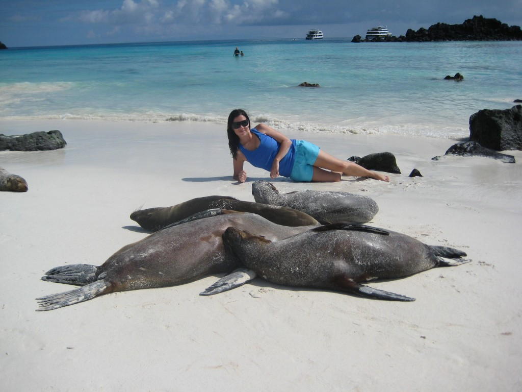 Woman lying with sea lions in the Galapagos Islands in Ecuador