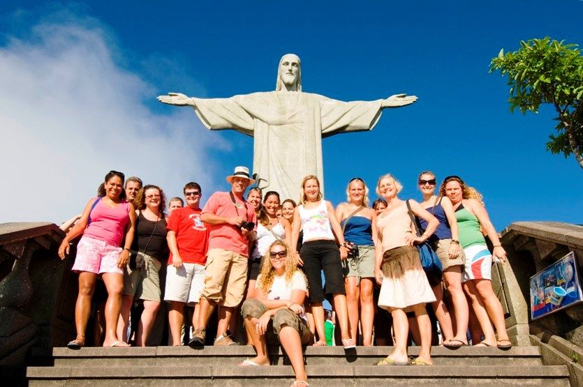 A group of tourists posing in front of Christ the Redeemer in Brazil