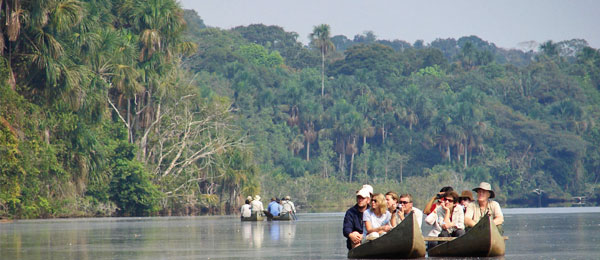 Tourists in canoes on a river in the amazon jungle