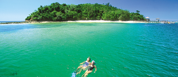 Couple snorkelling in the sea near an island in Borneo