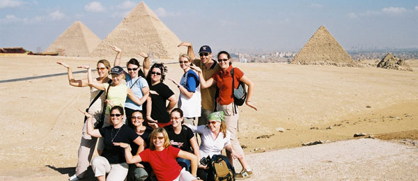 Tourists posing in front of the pyramids in Egypt