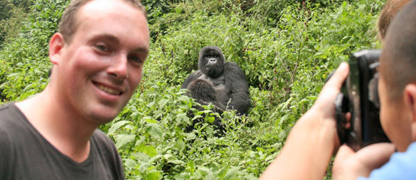 Man posing for a photo by a mountain gorilla in the Virungas National Park in Rwanda