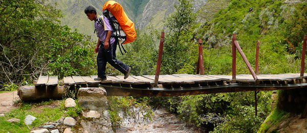A sherpa carrying a rucksack on a wooden bridge
