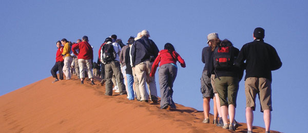 A group of tourists walking up a sand dune