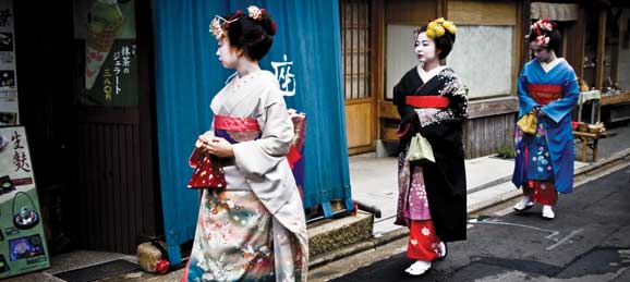 Geishas walking into a building in Japan