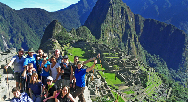 a group of hikers smiling in front of Machu Picchu