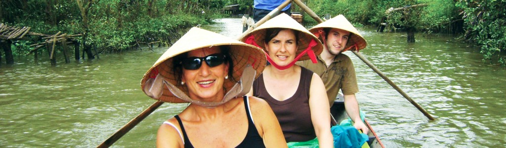 Tourists in traditional hats in a canoe on the Mekong River
